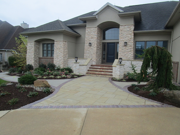 A blended red paver soldier course hugs a beautiful sandstone sidewalk, tying in varying hardscape textures and creating a striking contrast with the façade of the home.