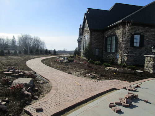 An expertly laid paver walkway curves invitingly around the grand entrance to the residence, highlighting planting beds and drawing the eye.