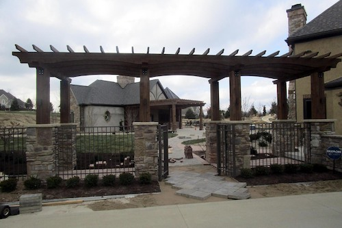 Elegant and purposeful, this stately pergola creates the perfect gateway into the charms of the backyard and visually connects the existing house with the new garage.