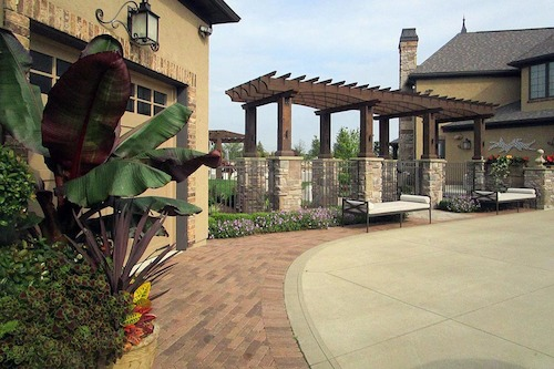 Simple plantings as you enter the backyard allow the charm of the pergola to take center stage.