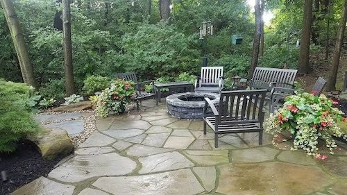 Each area is visually defined by the style of bluestone. Color choices and textures blend into the setting, while the patio's gentle, sweeping curves accentuate the natural tree line.