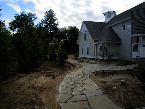 Crews lay out the sweeping, organic curves of the PA Bluestone walkway during construction.